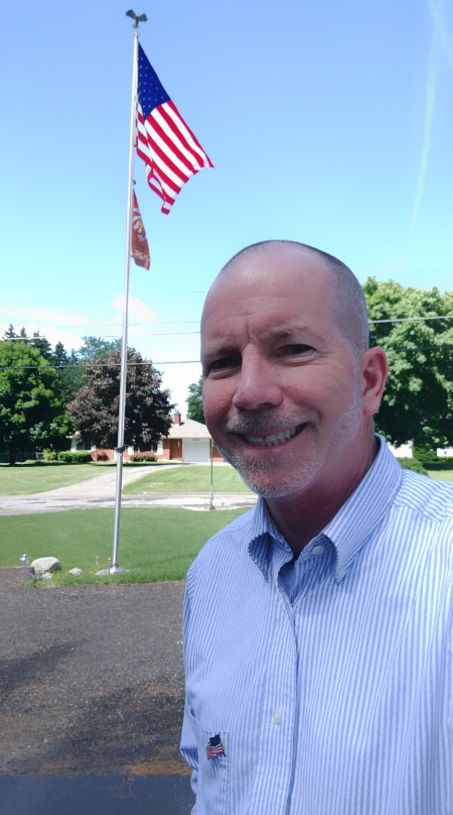 Trustee Tom Klee in front of an American flag